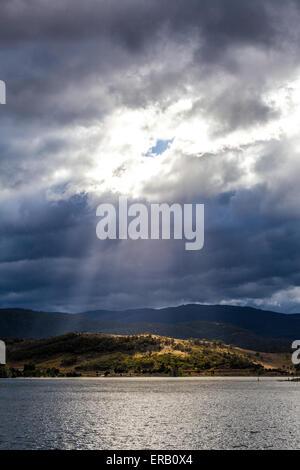 Strahlen der Sonne durch Wolken auf den Hügeln Lake Jindabyne, Australien - Stockfoto