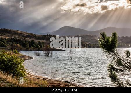 Die Strahlen der Sonne durch Wolken auf den Hügeln Lake Jindabyne, Australien. - Stockfoto