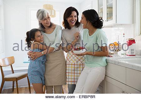 Generationsübergreifende Frauen lachen in Küche - Stockfoto