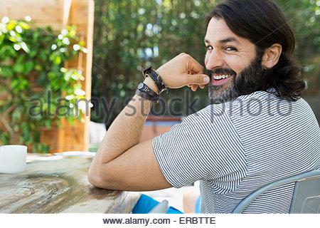 Porträt, Lächeln, bärtiger Mann an Terrassentisch drehen - Stockfoto