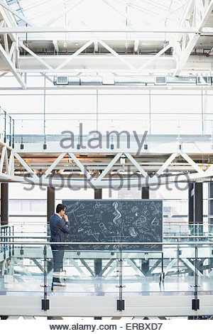 Geschäftsmann an der Tafel mit komplexen Gleichungen im atrium - Stockfoto