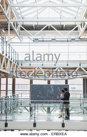 Business-Leute an der Tafel mit komplexen Gleichungen atrium - Stockfoto
