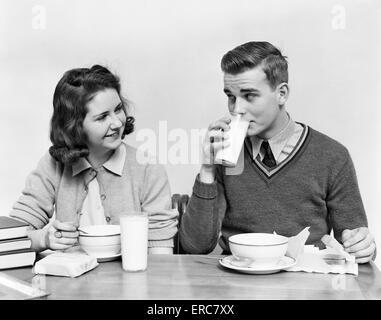 1940ER JAHREN TEENAGER MÄDCHEN UND JUNGEN ESSEN SCHULE MITTAGESSEN SUPPE SANDWICHES GEMEINSAM JUNGE TRINKT MILCH - Stockfoto