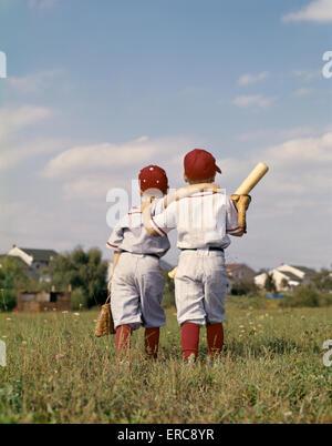 1960ER JAHREN ZWEI JUNGEN BRÜDER TEAMKOLLEGEN LITTLE LEAGUE BASEBALL TRAGEN UNIFORMEN GEHEN ARM IN ARM WEG VON DER - Stockfoto