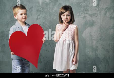 Niedlichen kleinen Jungen geben ein Herz für seine süßen Schwester - Stockfoto