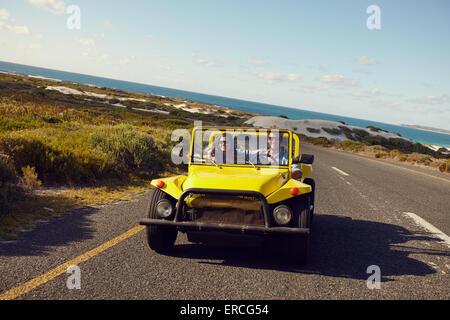 Junges Paar fahren in einem Auto auf einer Landstraße mit blauem Himmel und Meer im Hintergrund. Junges Paar auf - Stockfoto