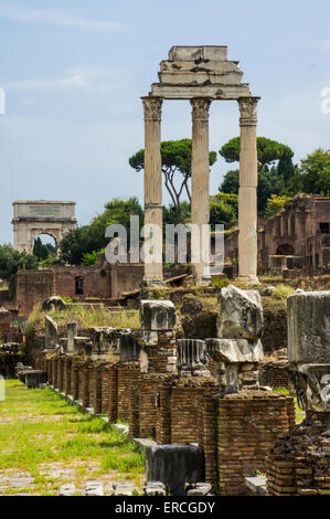 Drei Spalten bleiben aus dem Tempel des Castor und Pollux auf dem Forum Romanum in Rom. Bogen von Titus im Hintergrund. - Stockfoto