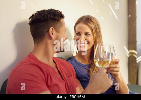 Glücklicher junger Mann und Frau bei einem Glas Wein in ihrem Hinterhof. Paar, toasten Wein und sahen einander Lächeln - Stockfoto