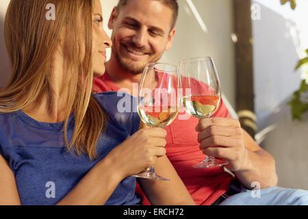 Closeup Aufnahme des jungen Mann und Frau sitzen zusammen Toasten Weingläser. Paar in Liebe romantische Zeit miteinander - Stockfoto