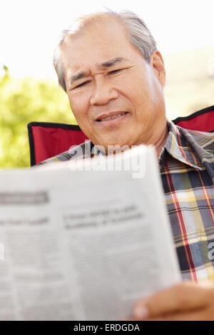 Senior asiatischen Mann liest im freien - Stockfoto