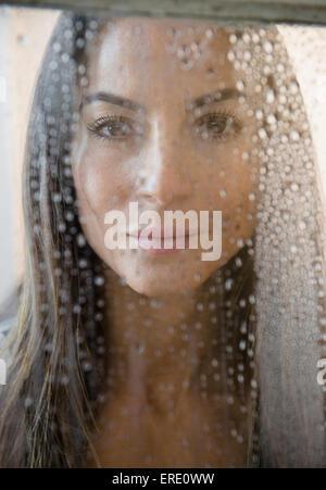 Kaukasische Frau spähte durch nasse Fenster Stockfoto