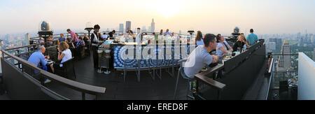 Bangkok, Thailand - April 15,2015: Sonnenuntergang über Bangkok aus einer Bar auf dem Dach mit vielen Touristen - Stockfoto