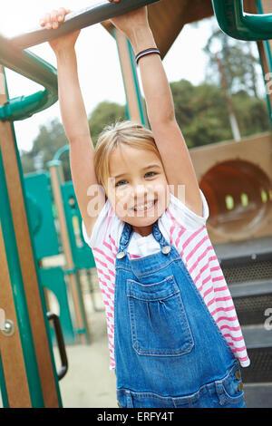 Junges Mädchen auf dem Klettergerüst auf Spielplatz - Stockfoto