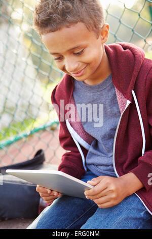 Kleiner Junge mit Digital-Tablette sitzen im Park - Stockfoto