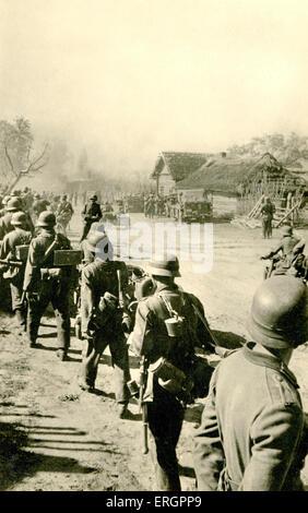2. Weltkrieg - Ostfront. Linie von deutschen Soldaten marschieren durch Land Dorf, Sowjetunion. Bildunterschrift - Stockfoto