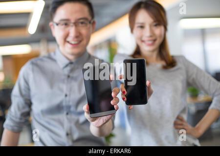 IT-Mitarbeiter zeigen Smartphone im Büro - Stockfoto
