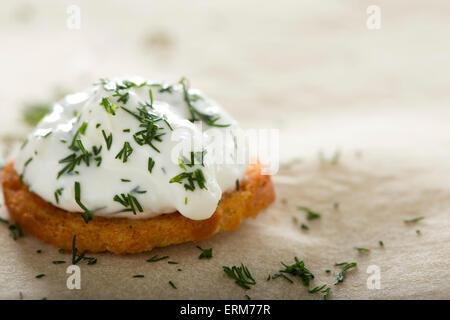 Nahaufnahme von einer Frischkäse mit Dill auf Backen Brötchen verteilen - Stockfoto