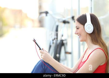 Frau von einem Tablet sitzen auf dem Boden in einem Park mit dem Fahrrad im Hintergrund Musik zu hören - Stockfoto