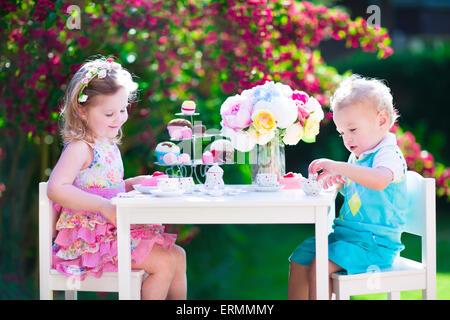 Tea Garden Party für Kinder. Kind Geburtstag feiern. Kleine Jungen und Mädchen spielen im freien heißen Schokolade - Stockfoto