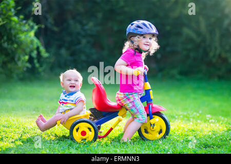 Zwei glückliche Kinder, entzückende lockige Kleinkind Mädchen und eine lustige Baby Boy, Bruder und Schwester, spielen - Stockfoto