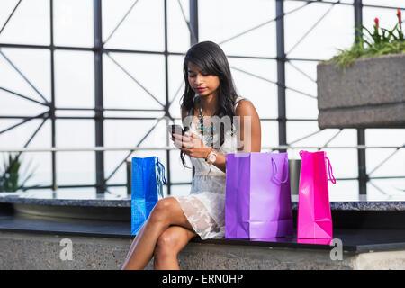 Junge professionelle Geschäftsfrau in der Innenstadt von Gebäude mit Einkaufstüten überprüfen ihr Smartphone; Edmonton, - Stockfoto