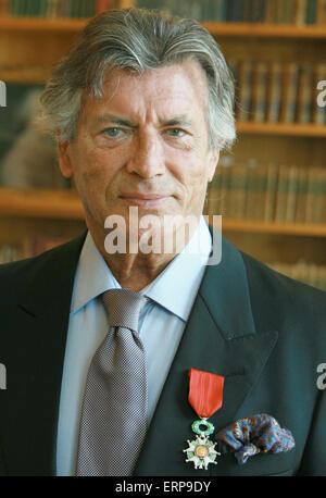Französischer Schauspieler Pierre Brice zeigt seinen Ausweis mit Band eines Ritters der Ehrenlegion, nachdem es - Stockfoto