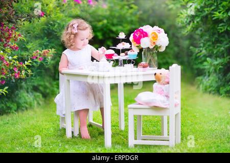 Entzückende Kleinkind Mädchen mit dem lockigen Haar trägt ein buntes Kleid an ihrem Geburtstag spielen Teeparty mit einer Puppe Teddybär