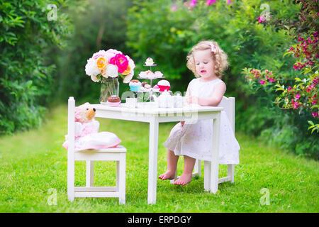 Liebenswert lustige Kleinkind Mädchen mit dem lockigen Haar trägt ein buntes Kleid an ihrem Geburtstag spielen Teeparty mit einer Puppe Teddybär