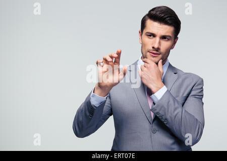 Schöne nachdenkliche Geschäftsmann berühren einen leeren Bildschirm unsichtbaren über grauen Hintergrund - Stockfoto