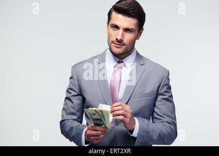 Gut aussehend Geschäftsmann zählen US-Dollar über grauen Hintergrund und Blick in die Kamera - Stockfoto