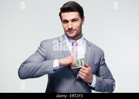 Geschäftsmann, Geld in der Tasche auf grauem Hintergrund. Blick in die Kamera - Stockfoto