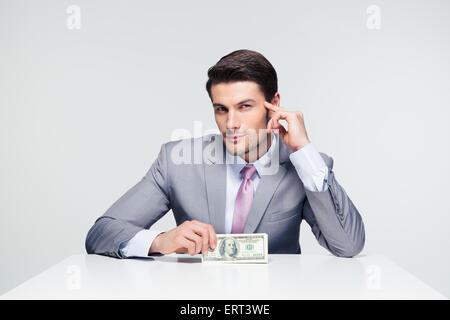Glücklich Kaufmann am Tisch sitzen und halten uns Dollarnoten über grauen Hintergrund - Stockfoto
