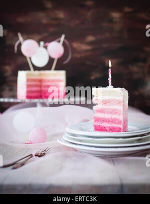 Stück Torte in rosa und weiß. mit Geburtstag Kerze drauf. - Stockfoto