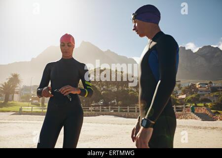 Aufnahme des jungen Mann und Frau mit ihren Badesachen im stehen am Strand. Triathleten, die Vorbereitung für das - Stockfoto