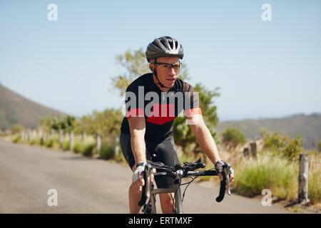 Mann Triathlon Sportler Radsportler, bergab auf Landstraße. Junger Mann Reiten Fahrrad auf offener Straße, üben - Stockfoto