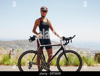 Porträt von überzeugt junge weibliche Radfahrer stehen mit ihrem Fahrrad auf der Landstraße. Fitness-Frau in Sportbekleidung - Stockfoto