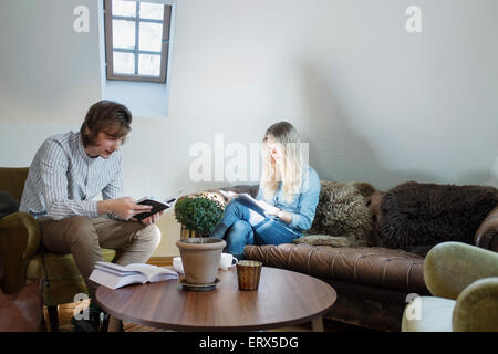 Männliche und weibliche Studenten lesen von Büchern im café - Stockfoto