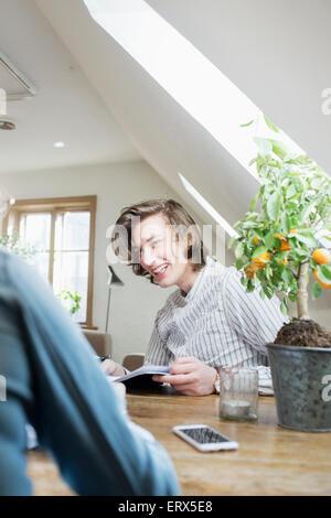 Glücklich Jüngling betrachten Freund während des Studiums in restaurant - Stockfoto