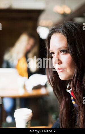 Nachdenkliche junge Frau wegschauen im café - Stockfoto