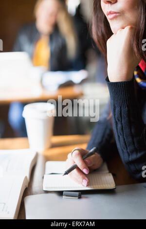 Bild der jungen Frau mit Tagebuch und Stift am Tisch im Café beschnitten - Stockfoto