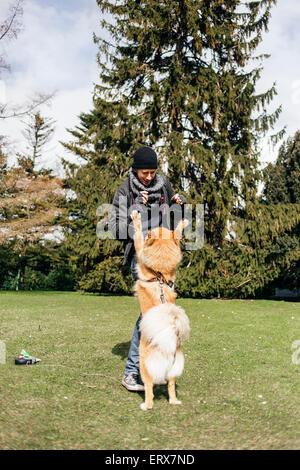 Junger Mann mit Eurasier im Park spielen - Stockfoto