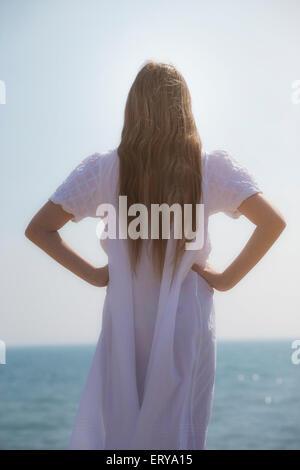 ein Mädchen in einem weißen Kleid von hinten - Stockfoto