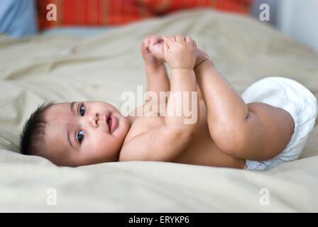 Sechs Monate alten Babymädchen spielt mit ihren Händen und Füßen auf Bett Herr # 447 - Stockfoto