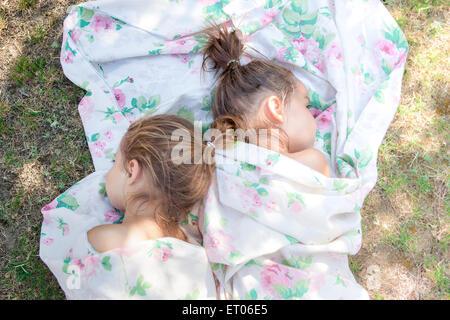 Zwillingsmädchen Nickerchen im floralen Blatt auf Rasen - Stockfoto