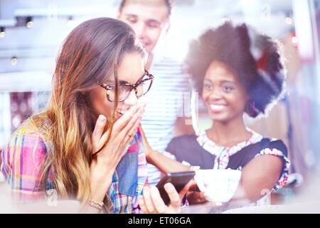 Lachenden Freunde SMS mit Handy im café - Stockfoto