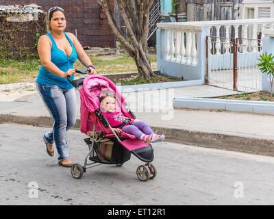 Dreißig etwas kubanische Mutter Spaziergänge, schob ihren kleinen Sohn in seinem Kinderwagen in Santiago De Cuba. - Stockfoto