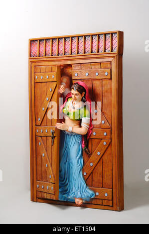 Tonfigur; Statue des Rajasthani junges Mädchen peeping aus halb geöffnete Tür - Stockfoto