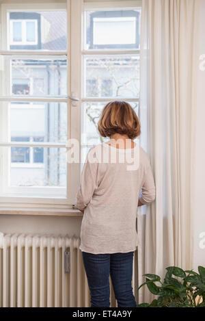 Rückansicht des senior Frau Blick durch ein Fenster, München, Bayern, Deutschland - Stockfoto