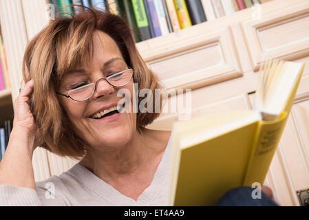 Ältere Frau beim Lesen vor Bücherregal, München, Bayern, Deutschland - Stockfoto