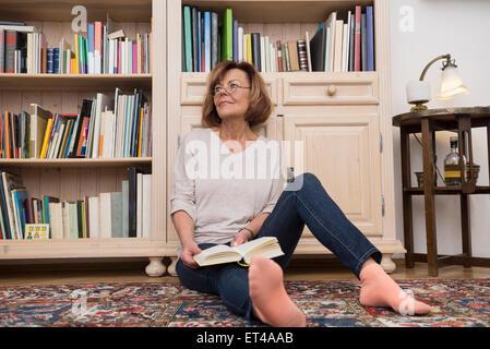 Ältere Frau sitzt auf dem Boden vor Bücherregal und Lesung, München, Bayern, Deutschland - Stockfoto